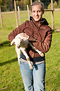 A farm helper holding a lamb.