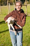 A farm helper holding a lamb.
