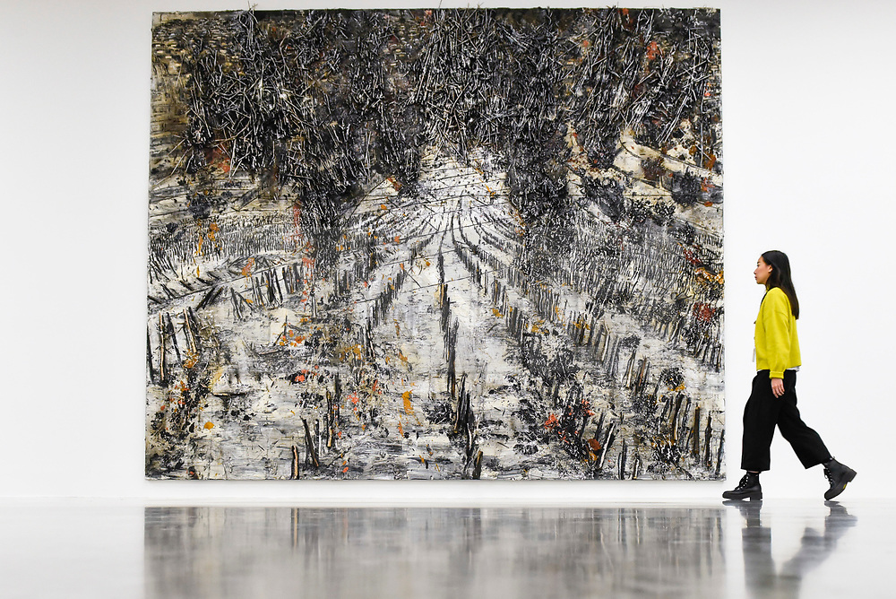 """© Licensed to London News Pictures. 14/11/2019. LONDON, UK. A staff member views """"String-Theorie"""", 2018-2019, by Anselm Kiefer at the preview of a new exhibition called """"Superstrings, Runes, The Norns, Gordian Knot"""" by Anselm Kiefer.  The works include large scale paintings and installations that draw on the scientific concept of string theory and are on display at the White Cube Gallery in Bermondsey 15 November to 26 January 2020.  Photo credit: Stephen Chung/LNP"""