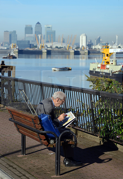 © Licensed to London news pictures. 06/10/2013. A man reading a newspaper in the sunshine in front of The Thames Barrier which is having its annual closure. The maintenance closure of the capital's flood defence system is being conducted by the Environment Agency. Spectators gathered to watch the iconic structure, known as the 8th wonder of the world close on a gloriously sunny Autum day. Credit : Mike King/LNP