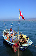 Fisherman sitting on his boat in the harbour, Fethiye, Turkey