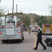 A Gallup Police officer sets up a perimeter at the corner of Third Street and Princeton Avenue in Gallup responding to the call of a house explosion Wednesday.