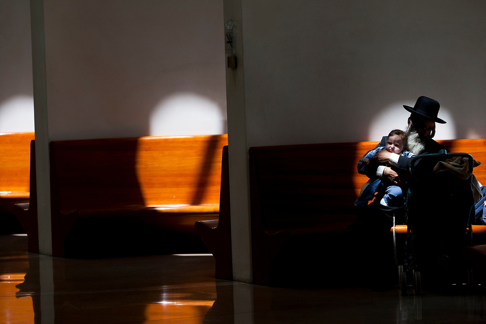 An ultra-Orthodox Jewish man tends to his child at the halls of the Supreme Court in Jerusalem, prior to a discussion regarding the segregation between Ashkenazi and Sephardic Jewish girls at the Beit Yaakov school in Immanuel, on April 29, 2010.