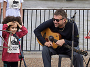 Damon Albarn singing for Extinction Rebelion with Mirabella Okri on 25th July 2021 outside Tate Modern, London, United Kingdom. 'Can't you hear the future weeping? Our love must save the world' is a statement by writer Ben Okri which was revealed in a live art piece by eco Artists Ackroyd & Harvey conceived as a message to us all, the artists were calling yet again for us to act in the face of our climate crisis. In the temporary 'greenhouse' of Tate, the seeds burst into life with the added dimension of Okri's clarion call to use active love to inspire the change we need. Stencilled letters, blocking the light, then removed, created the message within the grass. For the final act, in a solemn ritual, the grass banner was rolled up, carried out by volunteer performers and floated on the Thames. Visible from up high, floating on the tidal river, the luminescent yellow letters stood out boldly from the rich green of the grass. At the end of the day the banner was dismantled and the grass art distributed to anyone who wanted to continue to grow the words.