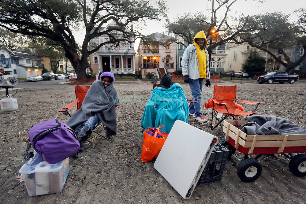 09 February 2016. New Orleans, Louisiana.<br /> Mardi Gras Day. Waiting for the parade. Revelers huddle for warmth in the early morning hours as they await the main Mardi Gras Parades of Zulu and Rex on St Charles Avenue.<br /> Photo©; Charlie Varley/varleypix.com