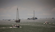 View of lake and oil drilling rigs from PDVSA oil drilling yard on Lake Maracaibo, Venezuela.