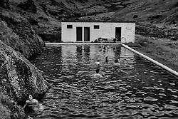 People swimming, in the natural geothermal swimming pool, Seljavallalaug, south Iceland - Ferðamenn í Seljavallalaug