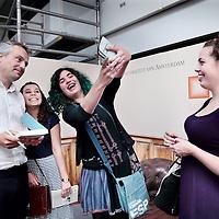 """Nederland, Amsterdam, 1 juli 2015.<br /> College met Joris luijendijk omtrent zijn laatste boek """"Dit kan niet waar zijn-onder bankiers aan de UvA in de Roeterstraat.<br /> Op de foto: na afloop kunnen studenten zijn boek laten signeren. enkele studentes maken samen met Joris luijendijk een selfie.<br /> <br /> <br /> Foto: Jean-Pierre Jans"""