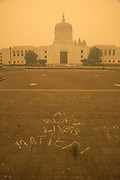 Chalk writing left over from Black Lives Matter protest at the Oregon State Capitol under the smoke from the 2020 Oregon wildfires.