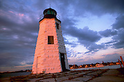 USA - Newport, RI - Green Light , light house on goat island with a pink light,  behind is a view of the Point area at sunset.