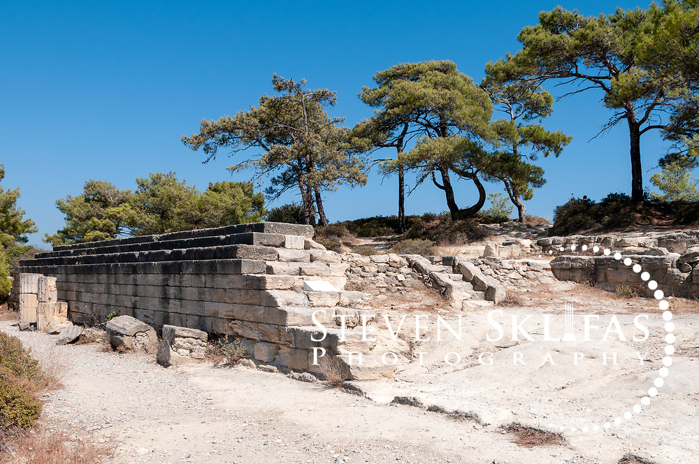Rhodes. Greece. Partial view of the ruins of the 3rd century BC Stoa which lined the north side for some 200 metres at Ancient Kameiros. Set idyllically on the west coast of Rhodes Island, the remains of Ancient Kameiros ascend a terraced pine covered hillside set against the blue waters of the Aegean Sea. The ancient city was founded by Althaemenes of Crete and was a thriving Classical Greek city during the 5th century BC; however successive earthquakes led to it being finally abandoned and buried by a massive earthquake 142 BC.  Rediscovered in 1859 when villages uncovered a few tombs and the city ruins provide a glimpse of the balance and serenity of urban planning in Hellenistic Greece. The island of Rhodes is the largest of the Dodecanese Island group and one of the most popular Greek Islands.