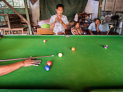 02 MARCH 2014 - MYAWADDY, KAYIN, MYANMAR (BURMA):  Men play pool in a pool hall in Myawaddy, Myanmar. Myawaddy is separated from the Thai border town of Mae Sot by the Moei River. Myawaddy is the most important trading point between Myanmar (Burma) and Thailand.    PHOTO BY JACK KURTZ