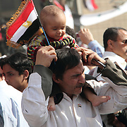 A father carries his tiny flag-waving son on his shoulders through Cairo's Tahrir Square during the Day of Justice and Cleansing.