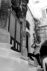 Fotografo si appresta ad inquadrare il portale della facciata di una probabile chiesa sconsacrata ed adibita ad una civile abitazione, come si vede dalla vetrata d'ingresso.