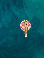 Aerial view of beautiful woman in bikini floating on inflatable lollipop mattress on Atokos island.