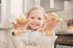 Girl hands covered with dough, smiling, portrait