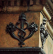 19th Century metalwork relief on the corner of a New York shopping street. The flourishing cornucopia and Greek semiology suggest Art Nouveau period décor.