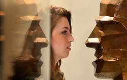 """© Licensed to London News Pictures. 15/11/2012. London, UK A woman looks at 'Large Bronze Head"""" by Eduardo Paolozzi. The Royal College of Art is celebrating its 175thanniversary with a major exhibition featuring more than 350 works of art and design by over 180 RCA graduates and staff, including Henry Moore, Barbara Hepworth, Tracey Emin, David Hockney, Peter Blake, Bridget Riley and Lucian Freud. The RCA is the world's oldest art and design university in continuous operation. Its first students comprised a small group of teenage boys; today it educates some 1,200 postgraduate students from 55 different countries.. Photo credit : Stephen Simpson/LNP"""