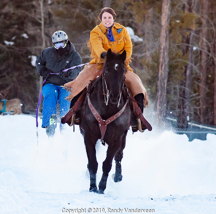 Photo Randy Vanderveen<br /> 2019-03-08<br /> Grande Prairie, Alberta<br /> Frank Hubbard stays close behind the hooves of a charging Oakley ridden by Darci Peterson at Thunder in the Pines at Evergreen Park Friday evening. The inaugural skijoring event, which saw someone on skis or a snowboard pulled around by a horse or horse and rider on a closed course proved a popular event at the Foster's Peace Country Ag Classic for both spectators and participants.