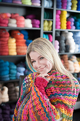 Portrait of a happy mature woman covering scarf in coffee shop, Bavaria, Germany