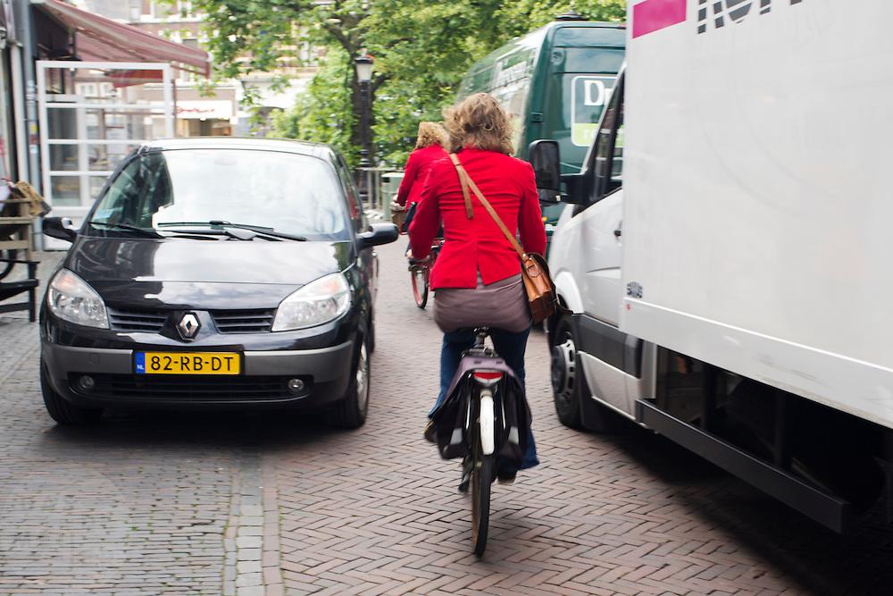 Een vrouw moet zich met de fiets tussen auto's door manoeuvreren.<br /> <br /> A woman has to maneuver her bike between the cars.