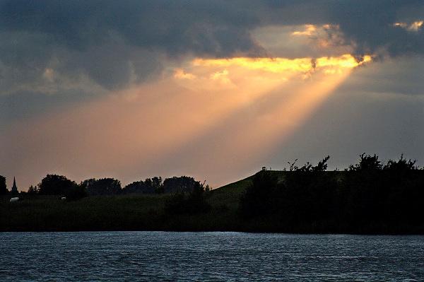Nederland, Schoonhoven, 7-6-2013De zon laat een stralenkrans boven het landschap van de rivier de Lek zien doordat ze door het wolkendek schijnt.Foto: Flip Franssen/Hollandse Hoogte