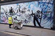 Streetsweeper passes a redeveloped, graffitied and gentrified shop front which is boarded up, empty and closed on Berwick Street in Soho on 1st December 2020 in London, United Kingdom. Once a seedy and wonderfully gritty street, Berwick Street has slowly been cleaned up as with much of the near vicinity, and so, with raising rents for shops, many small businesses have moved out.