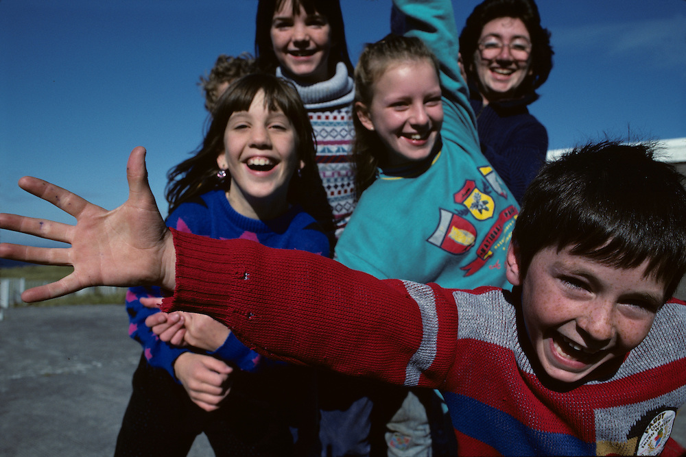 Europe, Ireland, School children clown during recess in Lettermore in County Galway on autumn afternoon
