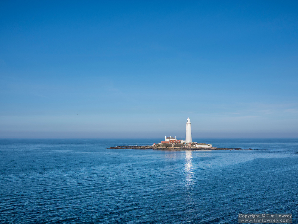 The Lighthouse on St Mary's Island Whitley Bay. The stark white of the lighthouse contrasts with the rich blue sky and the calm North Sea.