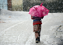 A Kashmiri young girl walks holding umbrella snowfall in Srinagar, the summer capital of Indian controlled Kashmir. Kashmir witnessed its first snowfall.