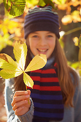 Smiling young girl holding a leaf