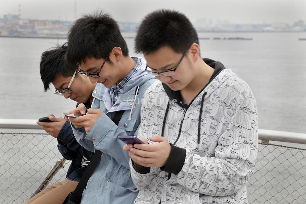 Japanese teenagers absorbed in their smartphones