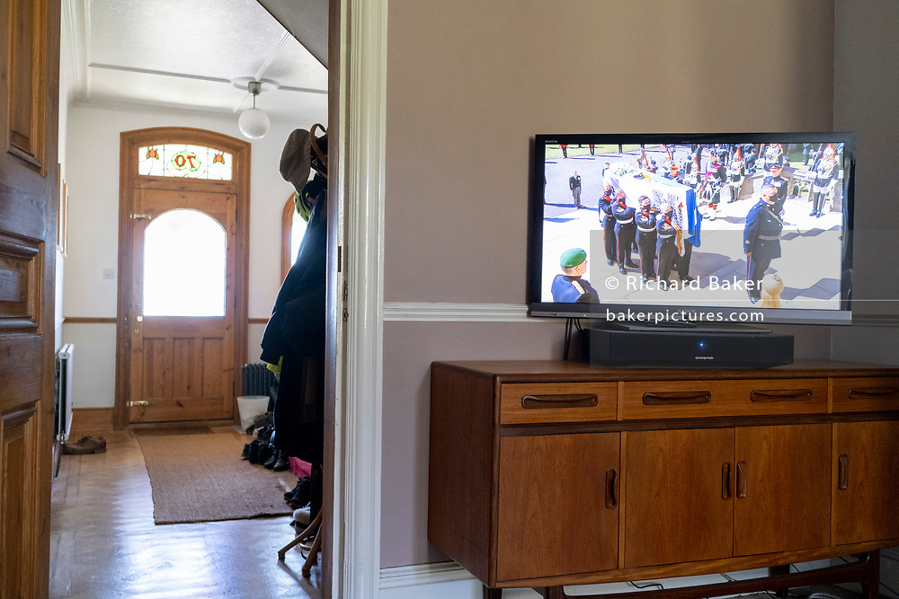 The funeral of Prince Philip, the Duke of Edinburgh, and husband to Queen Elizabeth II, is broadcast on British TV from Windsor Castle and watched in the living room by a south London family, on 17th April 20231, in London, England. Due to the continuing Coronavirus pandemic restrictions, the public have been urged to avoid joining crowds at large gatherings and instead, to watch the ceremony at home.