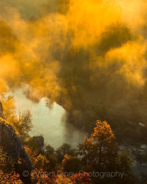 Autumn sunrise above a river in a gorge
