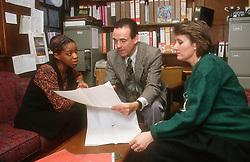 Three teachers meeting in head teacher's office discussing computer printout,