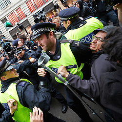 © Licensed to London News Pictures.  11/06/2013. LONDON, UK. A protester clashes with a police officer during an anti G8 protest in London ahead of the start of the conference in Northern Ireland. Photo credit: Cliff Hide/LNP