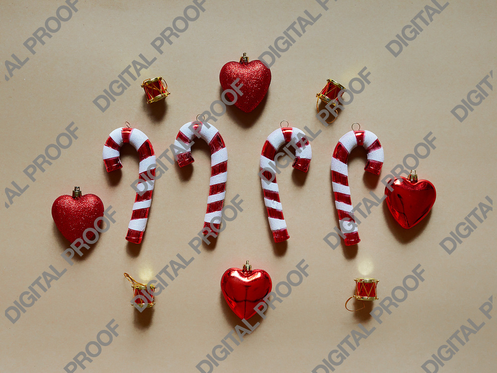 Christmas candy cane drums hearts and gifts at studio above view over a brown cream background isolated flatlay