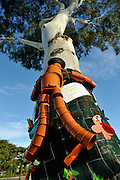 Public artwork on display as part of the annual Trunk Art Wrap Festival in Bassendean, Western Australia. All artworks are made entirely of recycled industrial or domestic waste materials.<br /> <br /> Made by a local pre-school group, this flowerpot man clings tightly to his tree.