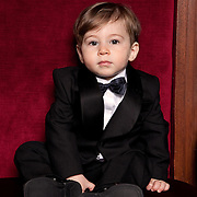 Little boy in tuxedo sits on big red chair