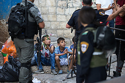 © Licensed to London News Pictures . 05/06/2016 . Jerusalem , Israel . Israeli soldiers separate youngsters in the Old City's Muslim district from thousands of Jews with flags processing through the Old City's Muslim district , on the way to the Western Wall . Israeli Jews celebrate Jerusalem Day . Photo credit : Joel Goodman/LNP