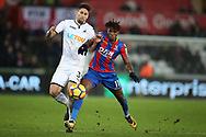Federico Fernandez of Swansea city (l) challenges Wilfried Zaha of Crystal Palace. Premier league match, Swansea city v Crystal Palace at the Liberty Stadium in Swansea, South Wales on Saturday 23rd December 2017.<br /> pic by  Andrew Orchard, Andrew Orchard sports photography.