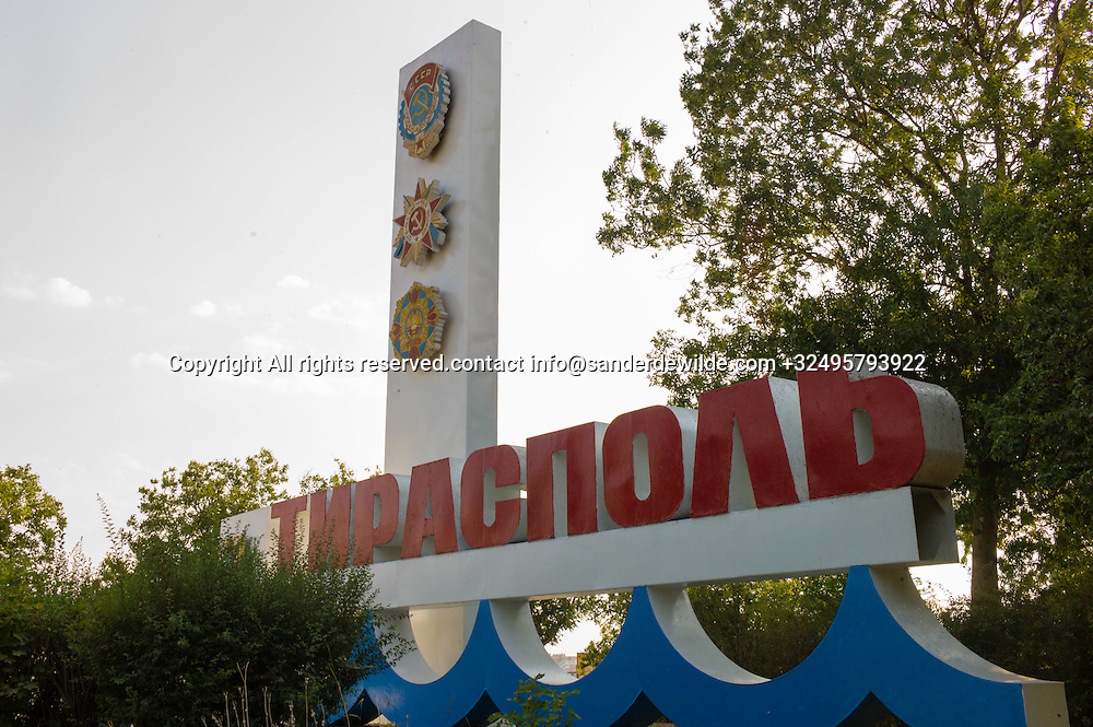 20150828  Moldova, Transnistria,Pridnestrovian Moldavian Republic (PMR) Tiraspol. a big concrete sign at the east entrance of Tiraspol, showing it's name in big red letters, floating on the blue river Dniestr, decorated with communist signs.