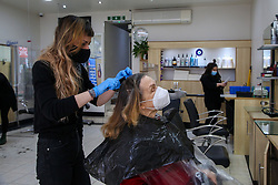 © Licensed to London News Pictures. 12/04/2021. London, UK. A woman gets her hair cut in a beauty salon on Green Lanes in Haringey, north London, which reopens after 4 months of Covid-19 lockdown. Cafes, restaurants, pubs, non-retail business and hairdressers across the UK closed following third national lockdown on 6 January, after a surge of coronavirus infections and hospital admissions across the UK. As restrictions are eased, cafes, restaurants, pubs, non-retail business and hairdressers reopen today. Photo credit: Dinendra Haria/LNP