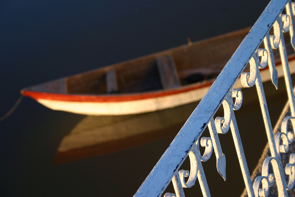 Row Boat lies in Lake Chapala, with balcony railing in foreground, Mexico