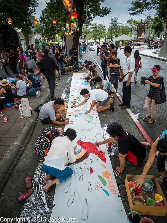 """06 JULY 2015 - BANGKOK, THAILAND: People paint a mural on a roll of paper during protest to support 14 Thai students arrested for violating rules related to a prohibition against political assembly in Thailand. More than 100 people gathered at Thammasat University in Bangkok Monday to show support for 14 students who were arrested two weeks ago. They face criminal trial in military courts. The students' supporters are putting up """"Post It"""" notes around Bangkok and college campuses up country calling for the students' release.      PHOTO BY JACK KURTZ"""