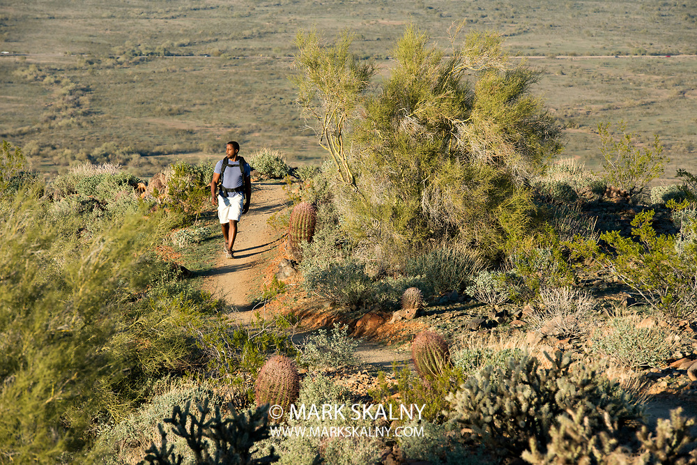 Young man and woman hiking outdoors on a trail at Phoenix Sonoran Preserve in Phoenix, Arizona.
