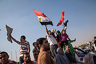 Muslim Brotherhood supporters shout and wave posters and flags infront of military vehicles outside Nassr City in Cairo.