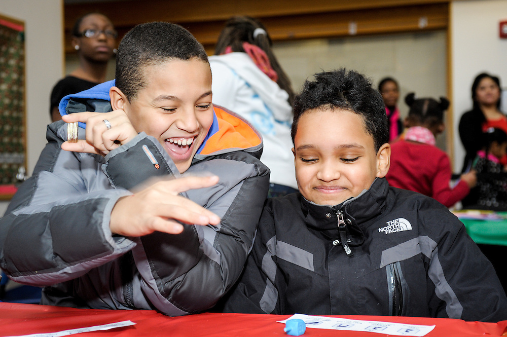 Two boys play dreidel at the annual Goodwill Holiday Party held at the organization's headquarters in Roxbury, MA.