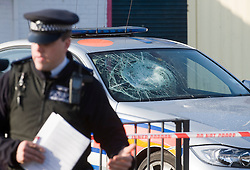 © London News Pictures. 19/11/2011. Police and forensics examine a police car which was attacked during the pursuit of a man who later stabbed four police officers on Kingsbury Road, North West London. A man attacked the police officers with a knife he grabbed from a local butchers shop after he had been chased by the police. Photo credit : Ben Cawthra/LNP