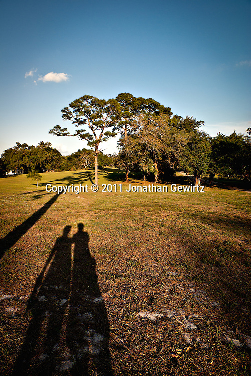 Late-afternoon shadows of two people standing next to each other in a grassy field with trees and sky in the background. WATERMARKS WILL NOT APPEAR ON PRINTS OR LICENSED IMAGES.